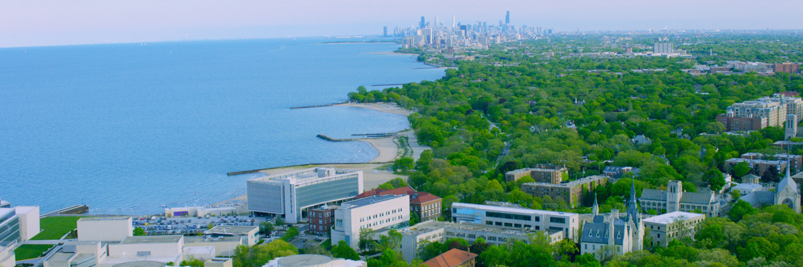 Drone photo of the Evanston campus along Lake Michigan with Chicago skyline in the background.
