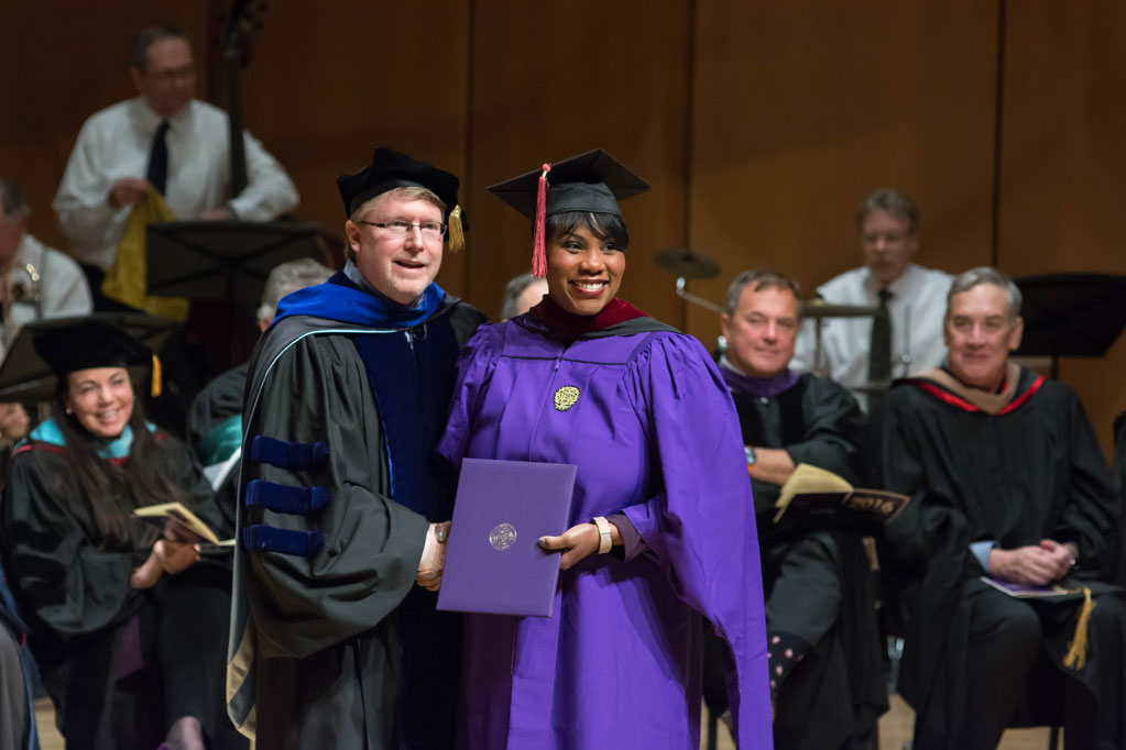 Dean Brad Hamm presents and IMC student with her diploma at graduation