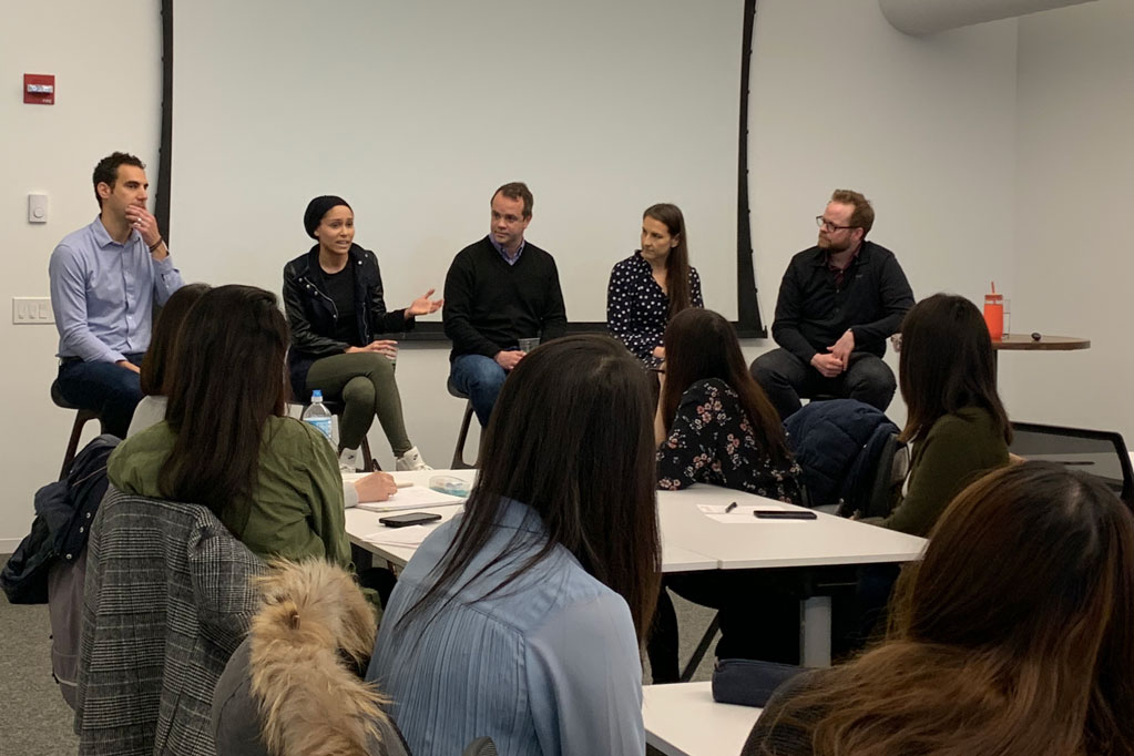 A panel of five people sit on chairs at the front of a room and speak to a group of students who are seated at tables