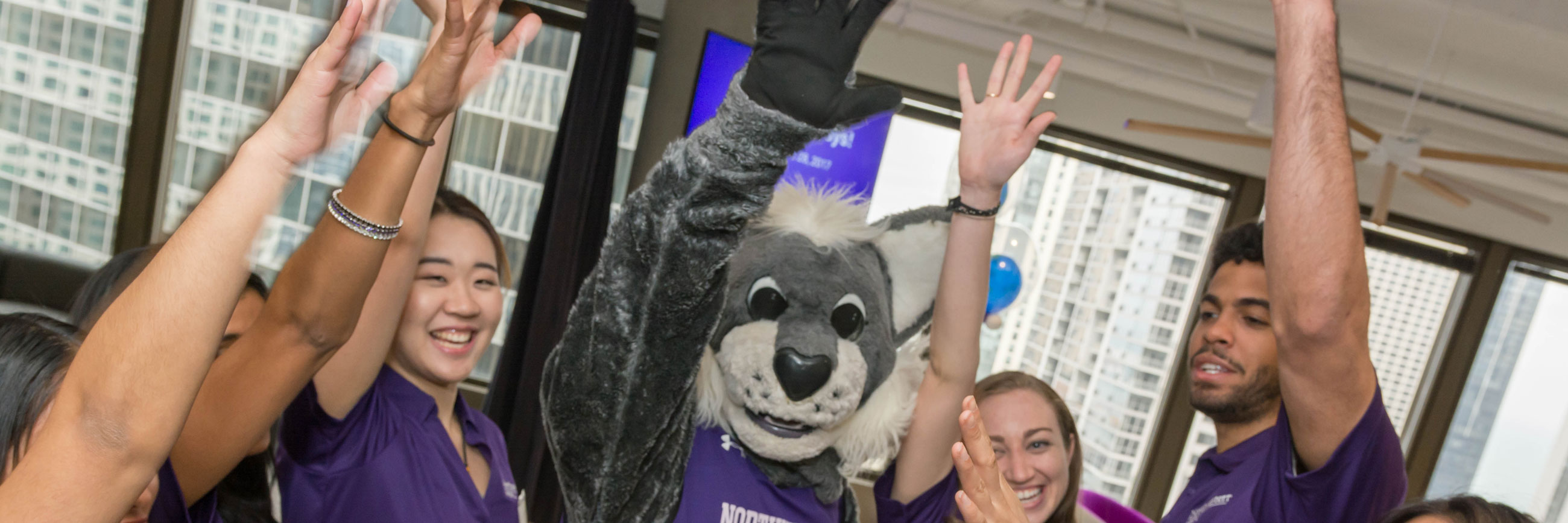 Students raise their hands in excitement with Willie the Wildcat