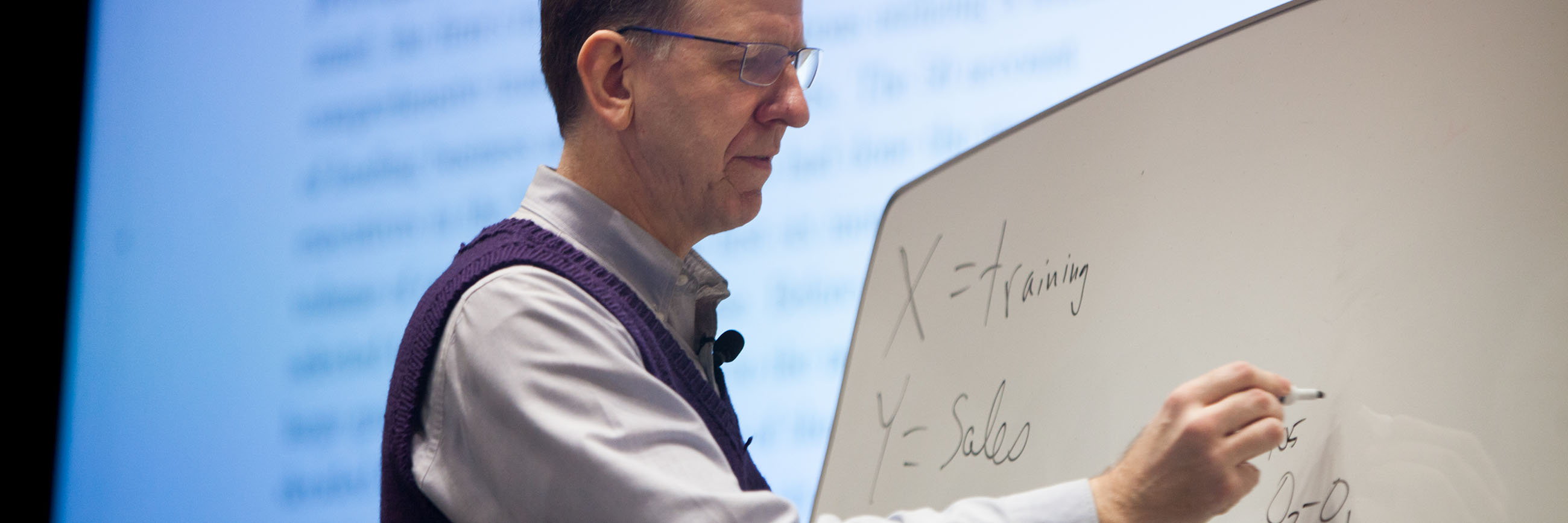 Faculty member writing on a white board.