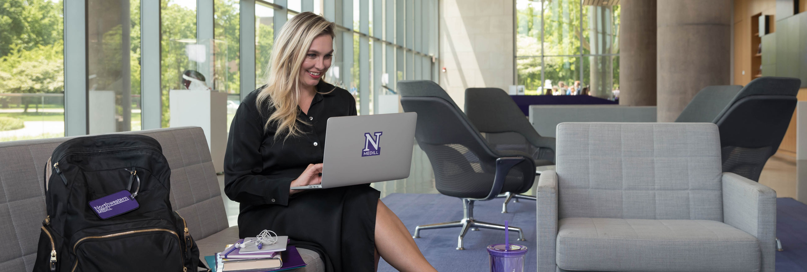 A student sits in a modern work space and works on a laptop computer while sitting on a couch