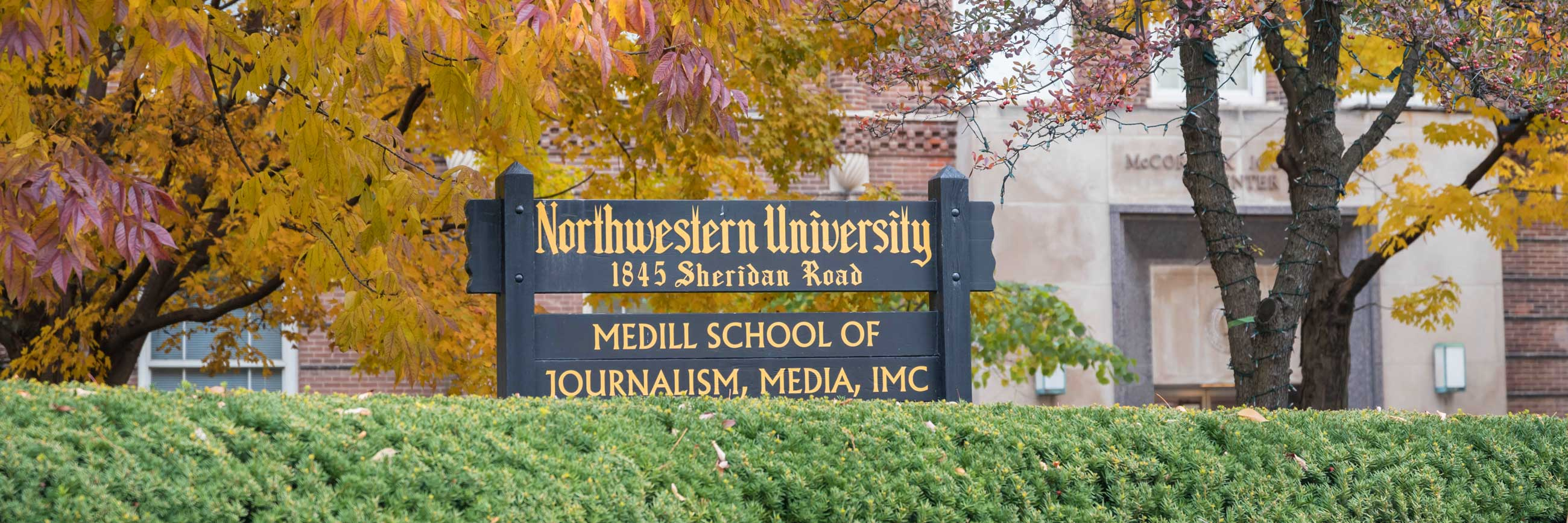 "A brick building with trees and a sign that says ""Medill School of Journalism Media IMC"""