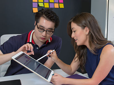 Two IMC students work on a project together on an iPad