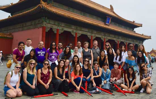A large group of students and faculty pose for a picture in the Forbidden City in Beijing, China