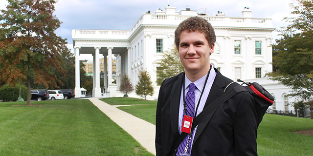 Student in front of White House with press pass