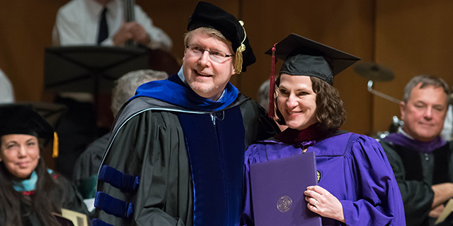 Online IMC student receiving her diploma at graduation in Evanston, Illinois