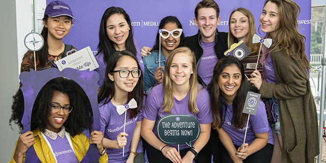 Medill undergraduate students pose for a photo wearing purple shirts and holding props
