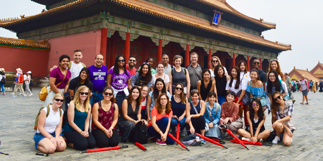 Students and faculty pose for a photo in front of the Great Wall of China