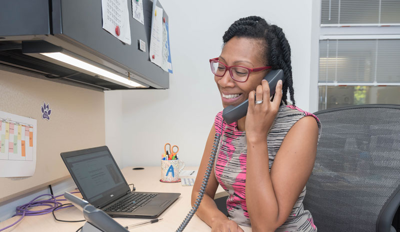 A career coach talks to a student on the phone while sitting at her desk