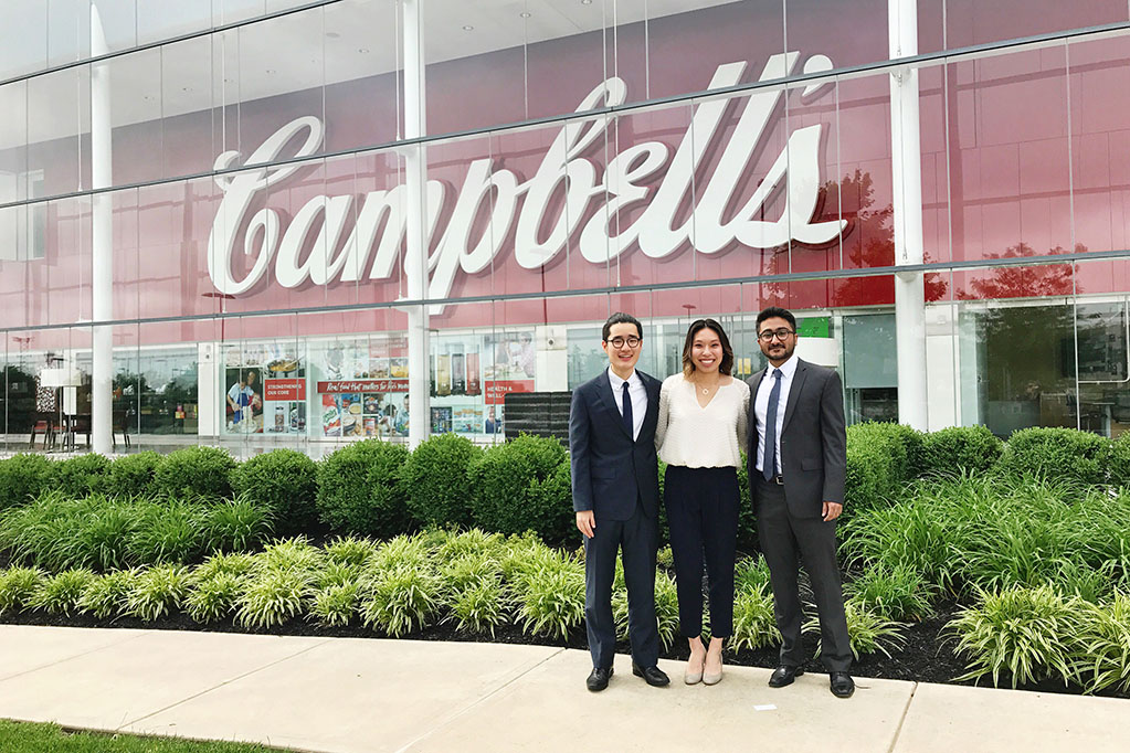 Students standing in front of Campbell's soup sign.