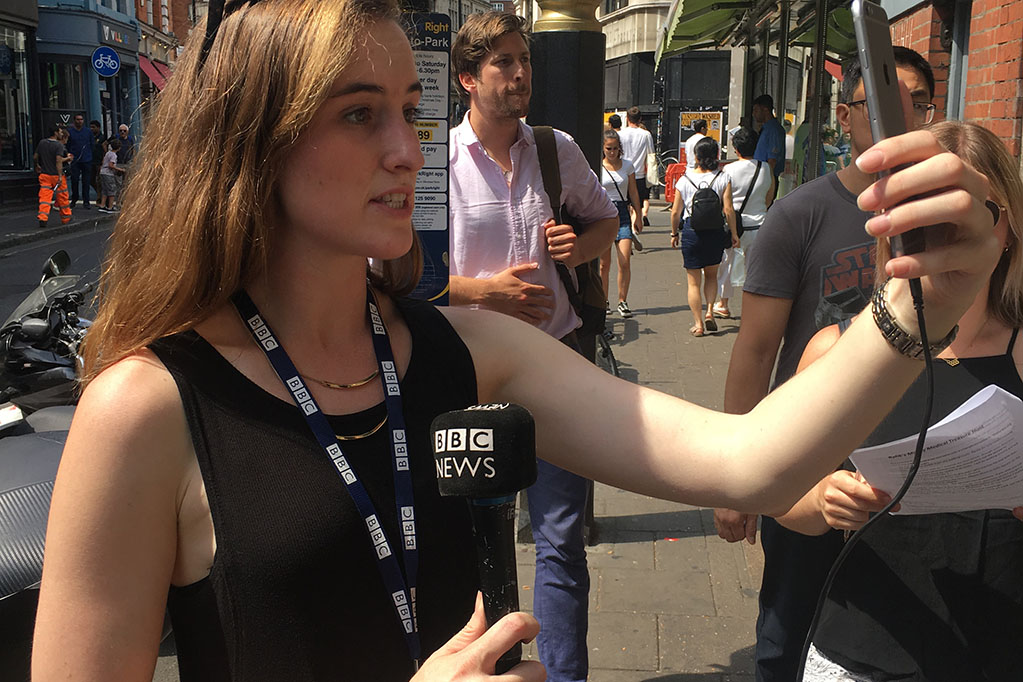 Student holding BBC microphone on London street and using iphone to boradcast report.