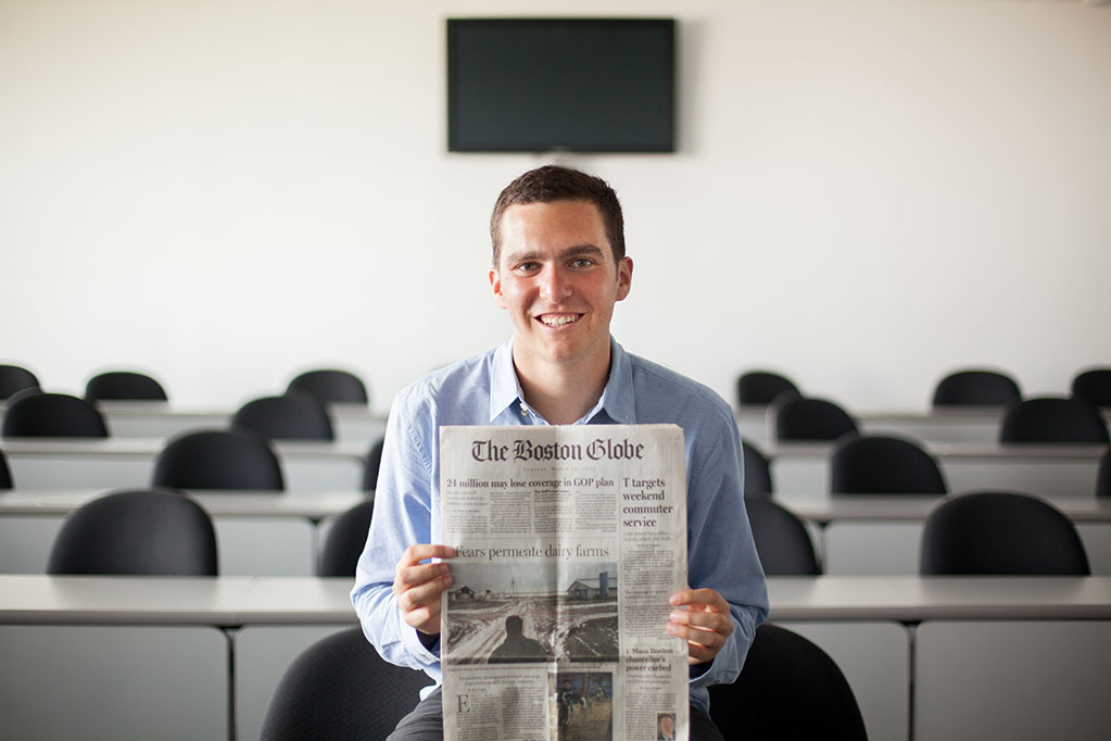 Tyler Pager holding up the front page of The Boston Globe