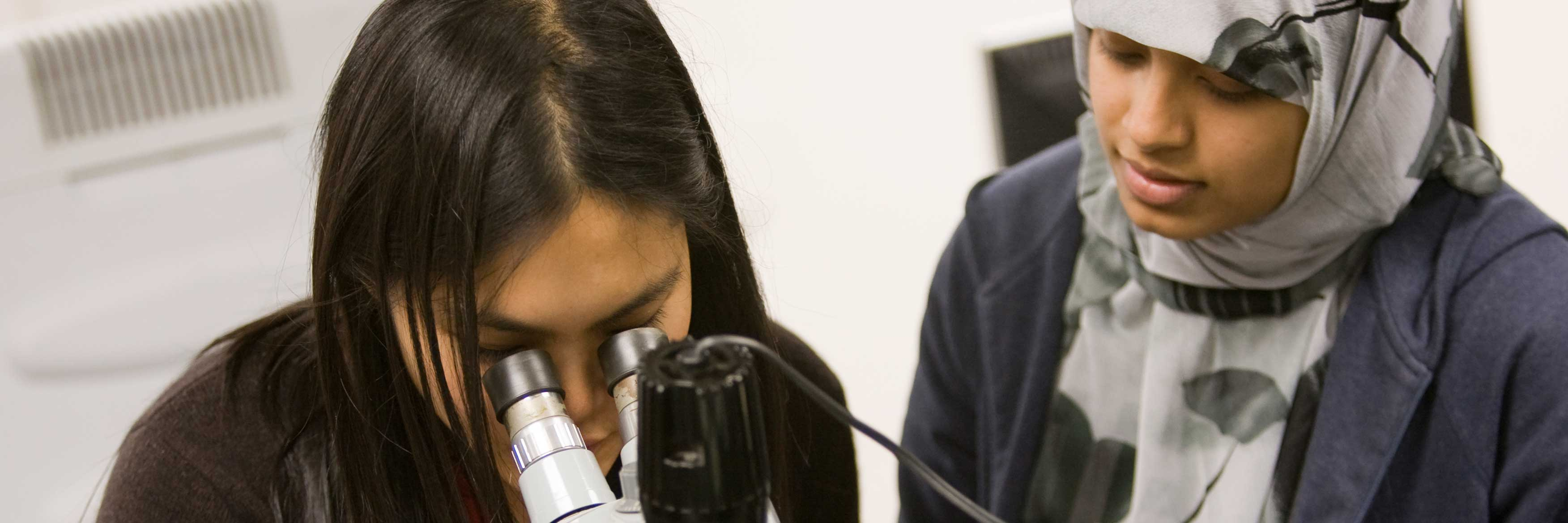 Two female students using a microscope
