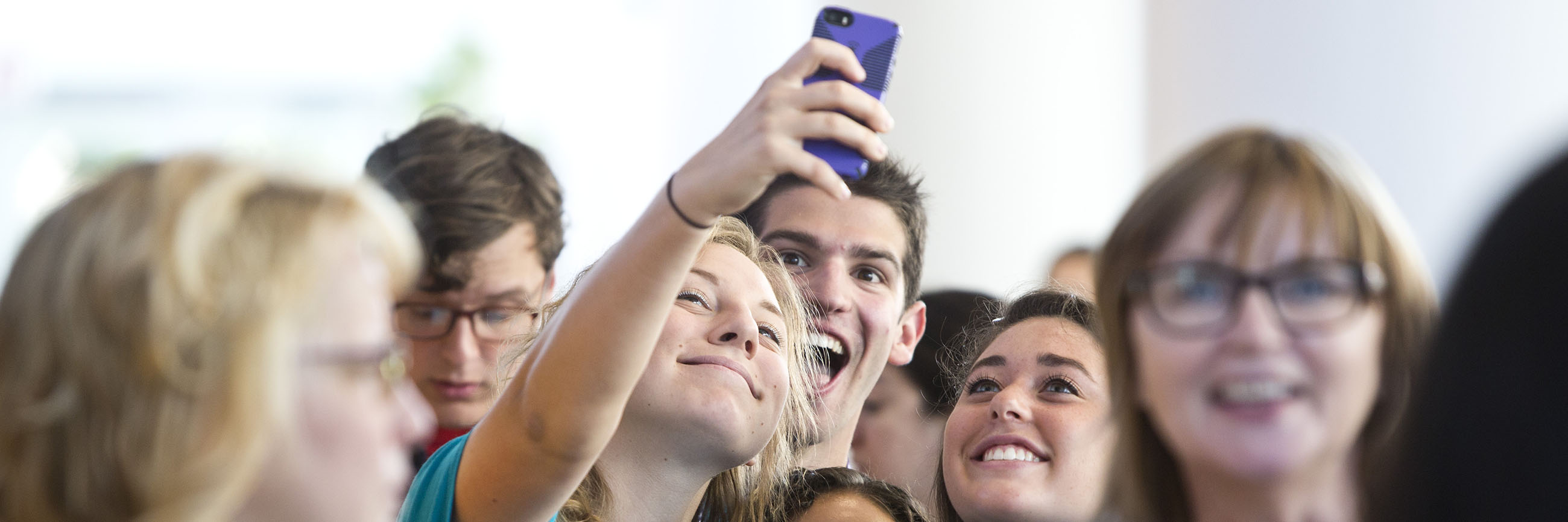 Student smiling and taking a selfie in a group.