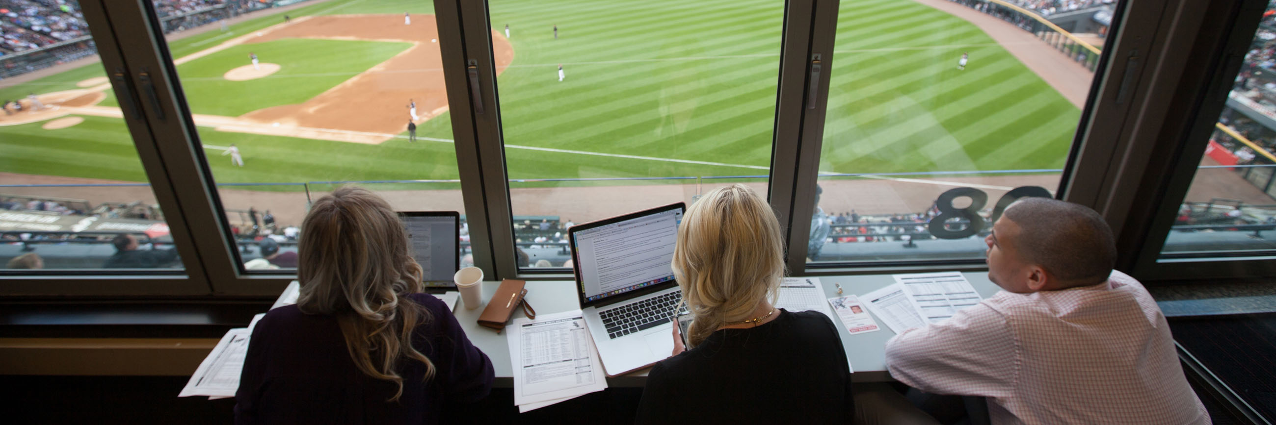 Students in the press box at a baseball game.