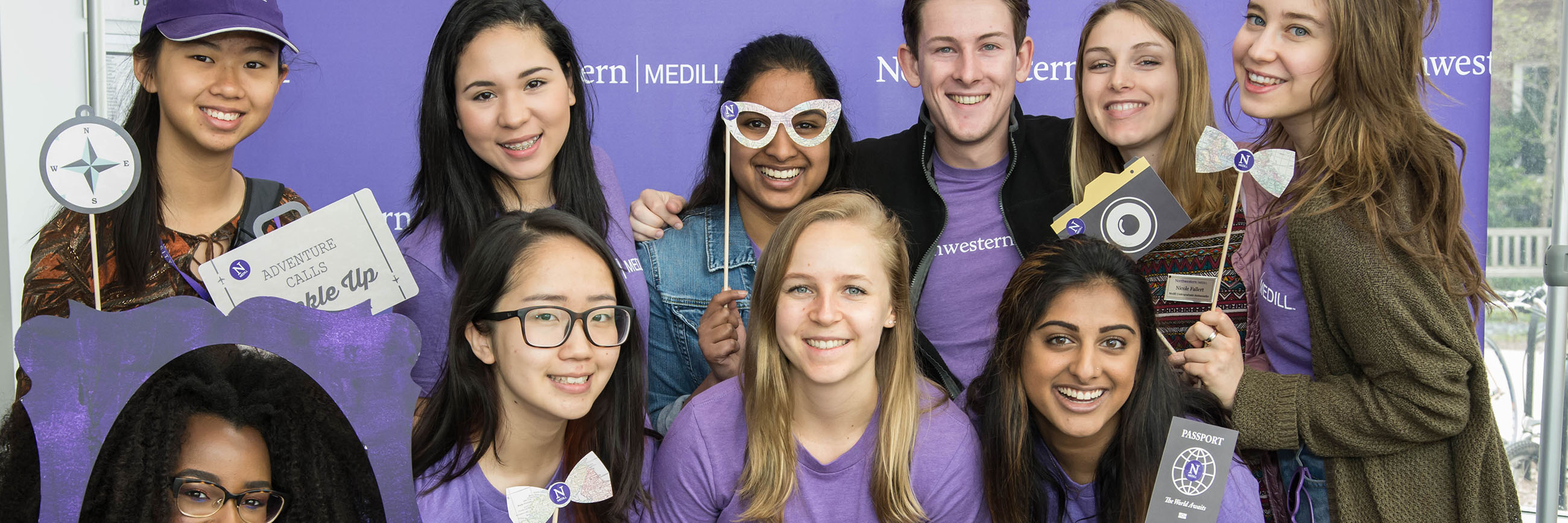 Students with fun accessories posing for a photo in front of Medill banner at Wildcat Days.