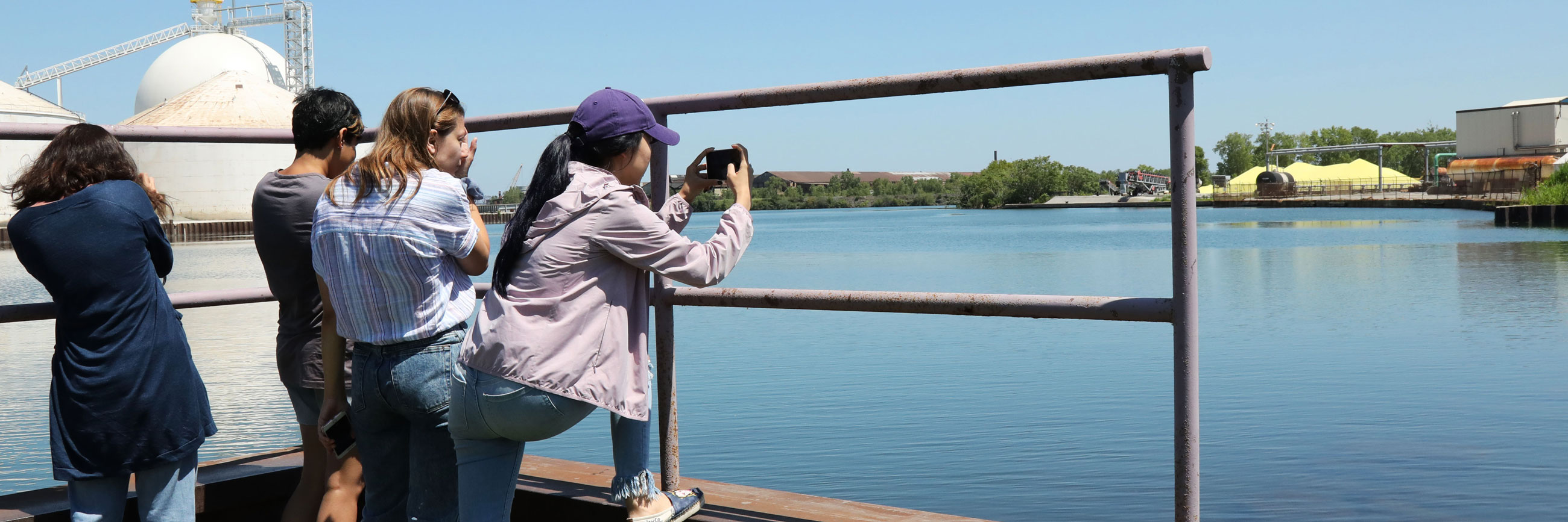 Students take photos of water plants during a reporting project