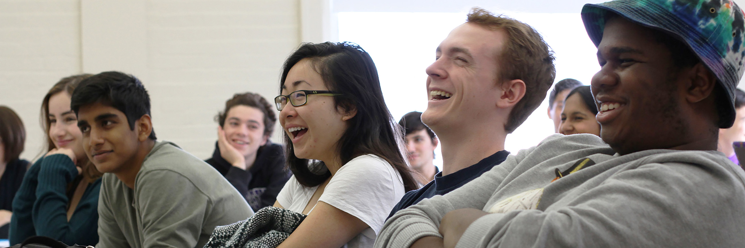 Students sitting in classroom laughing together.