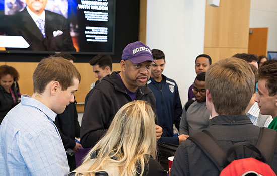Michael Wilbon, ESPN commentator and former sportswriter and columnist for The Washington Post, surrounded by students that he is talking to
