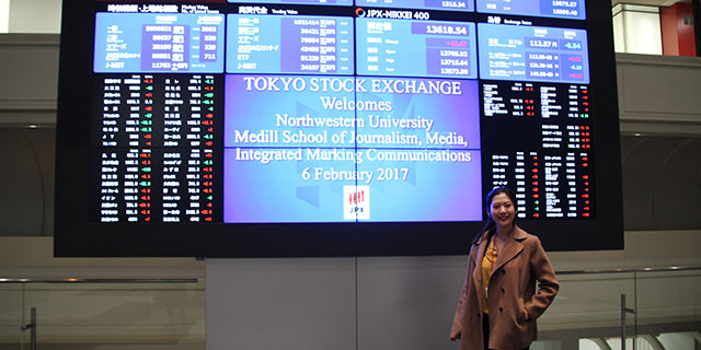 Student standing in front of the Tokyo Stock Exchange digital board.