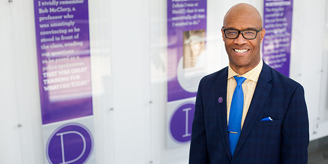Dean Charles Whitaker smiles in a Medill hallway.