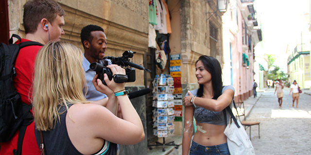 Students filming with a camera in Cuba.