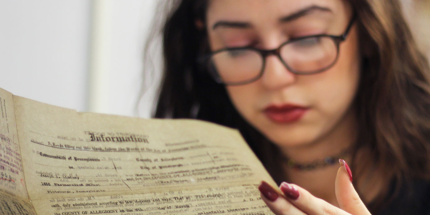A student reads old records as she works on a story