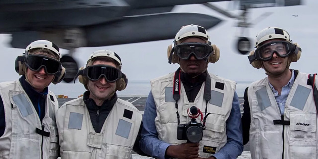 Four people stand on a Naval carrier wearing helmets and protective glasses and headphones.