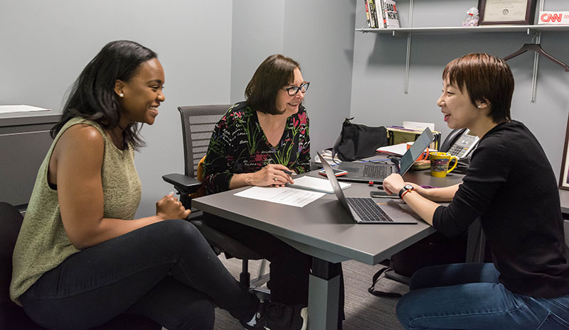 A faculty member speaks with two students who are sitting around a table