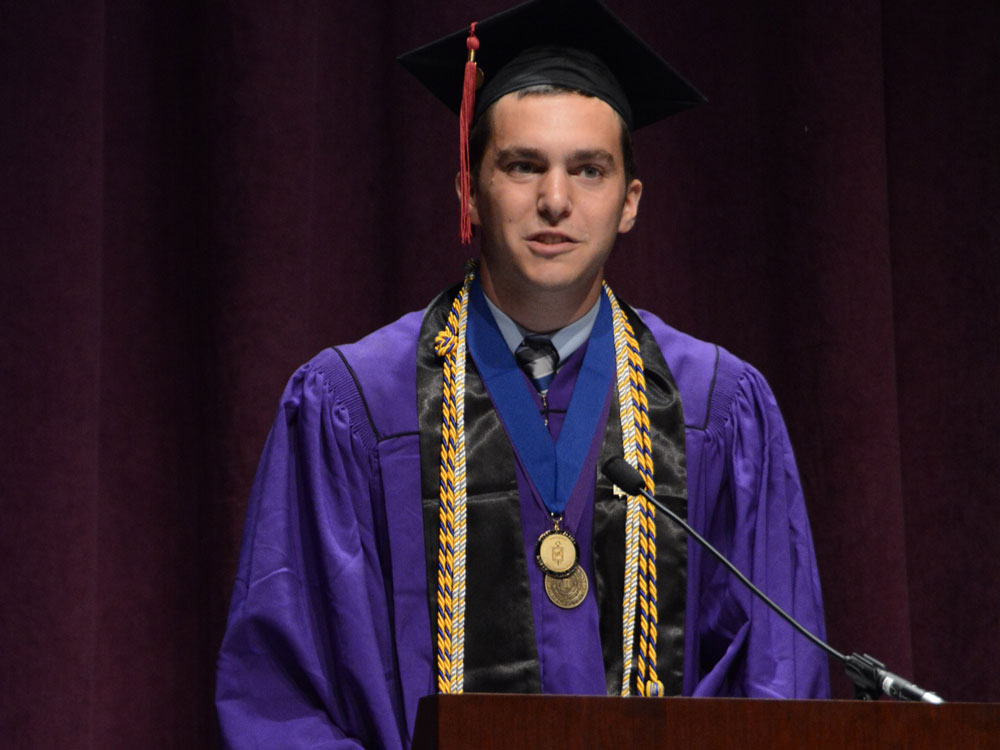A male student stands behind a podium and speaks; he is wearing a purple graduation cap and gown