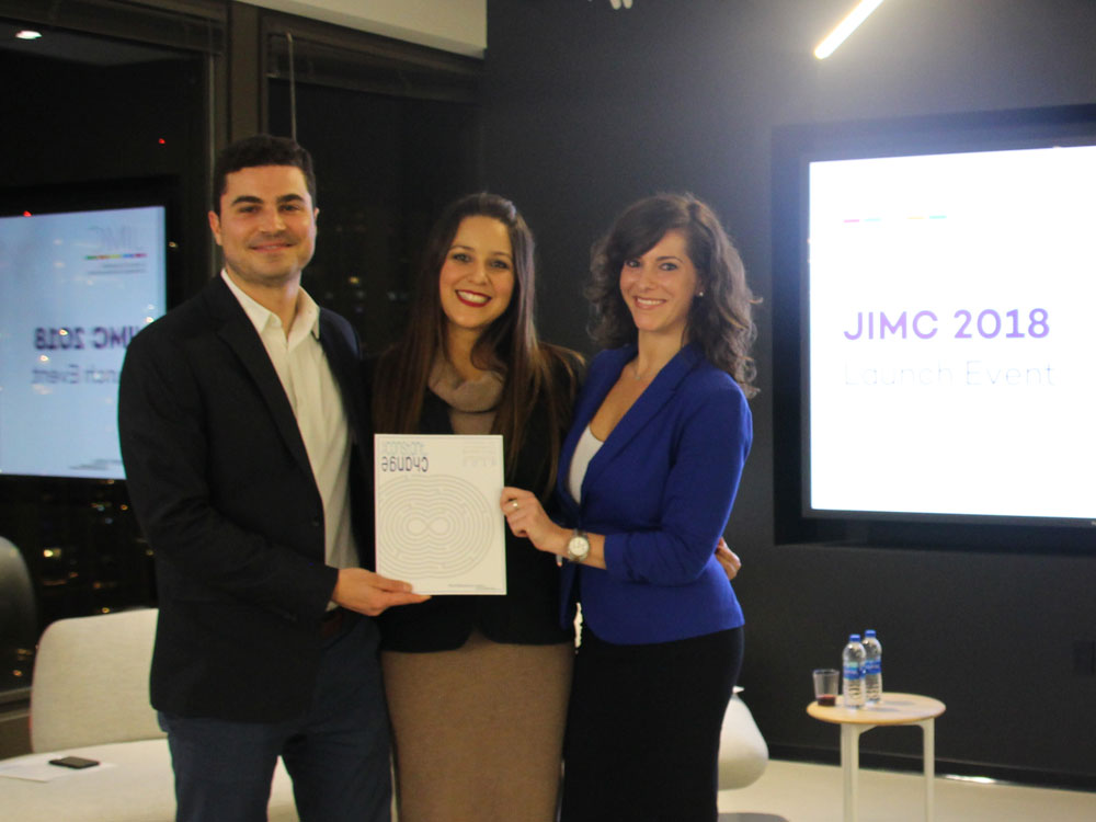 Three students stand together and hold a copy of the new edition of JIMC at the Medill Chicago launch event