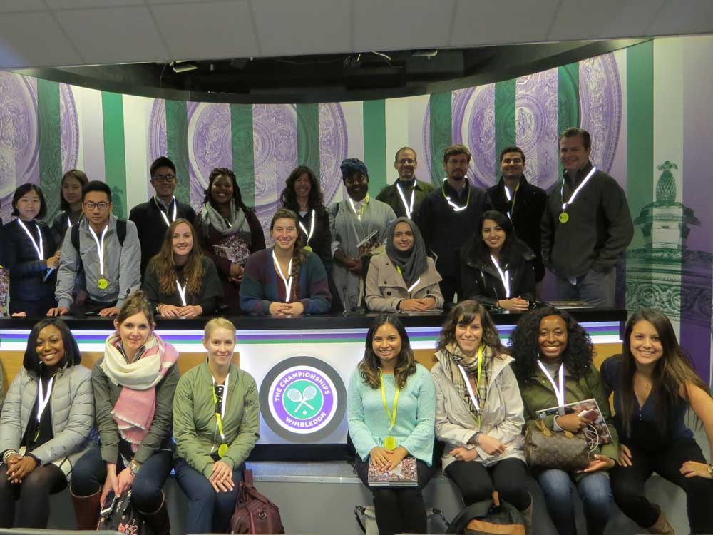 A large group of students sit at a desk at Wimbledon in London