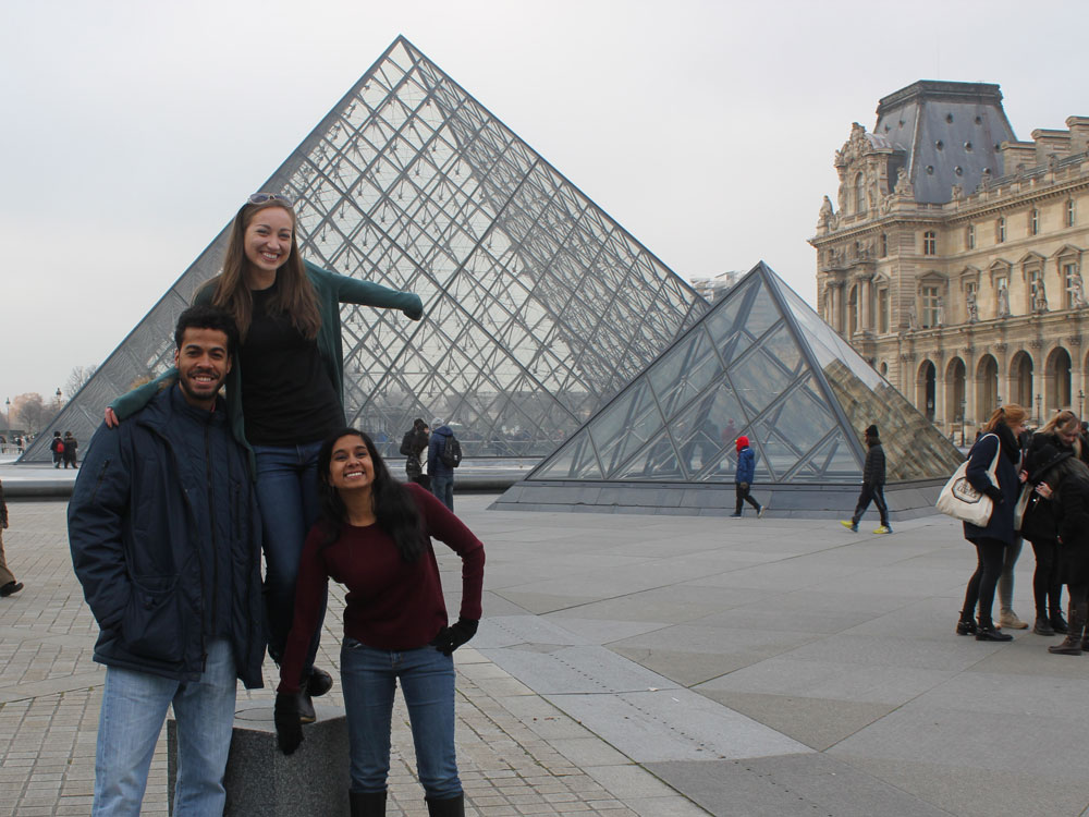 Three Medill IMC students pose for a photo in front of the Louvre Museum in Paris