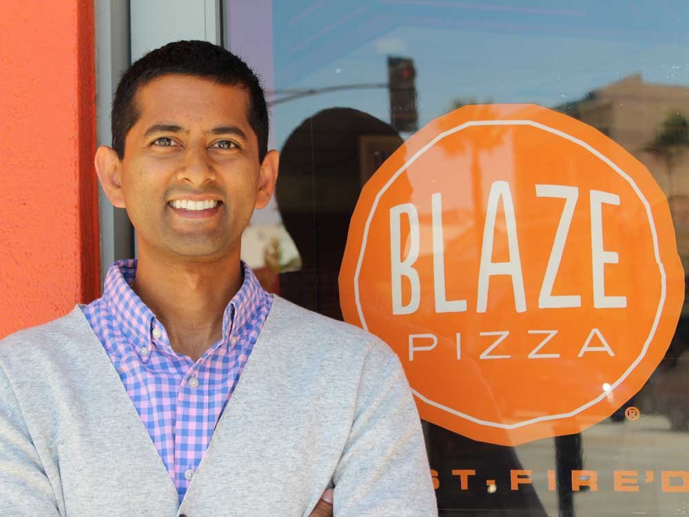 A man stands in front of a glass window with the Blaze Pizza logo on it