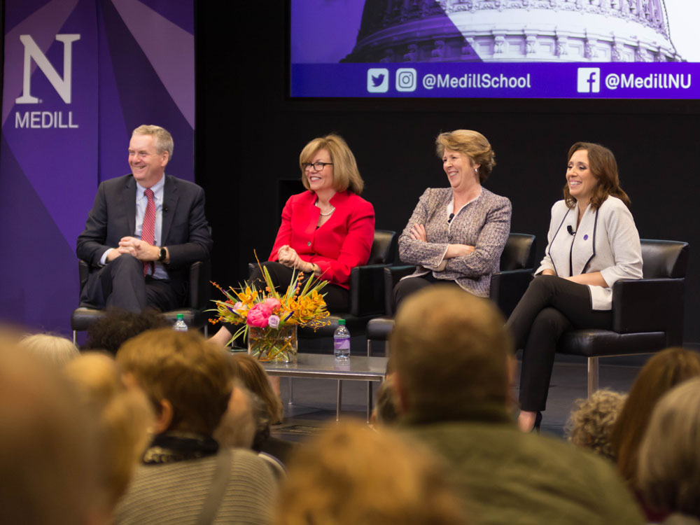 Three women and one man sit on stage during a panel discussion and smile at the crowd