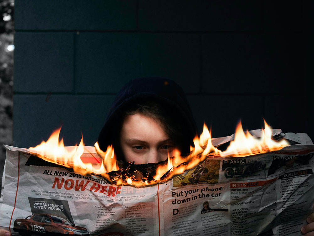 Photograph of a person reading a newspaper that is on fire.