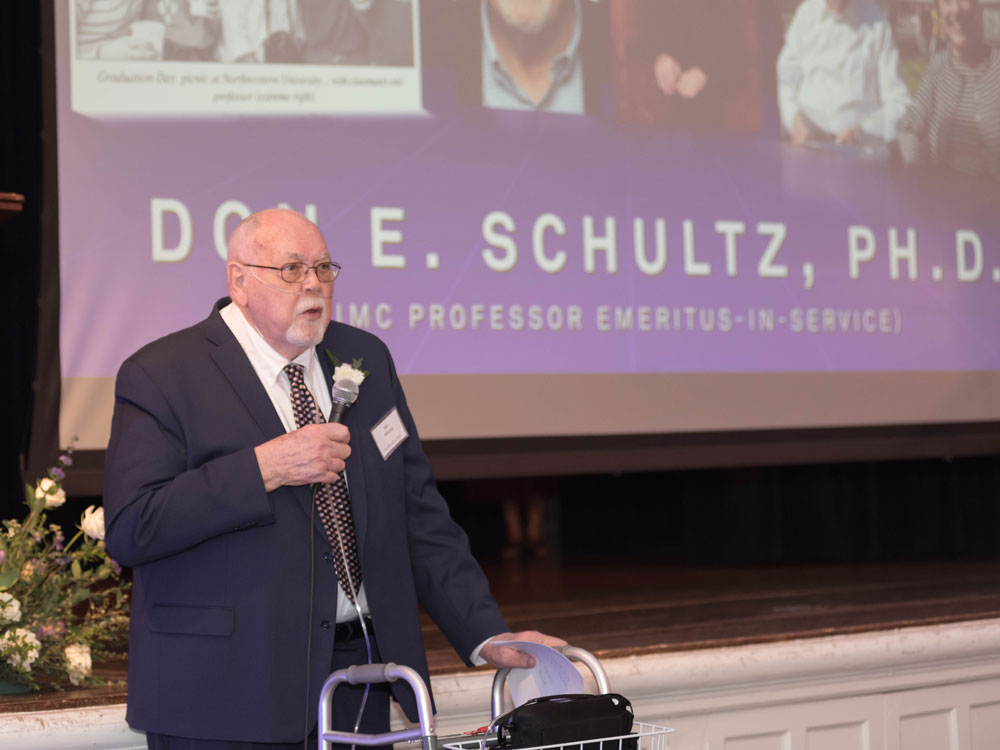 Don Schultz stands at the front of a room and speaks into a microphone at the Hall of Achievement reception