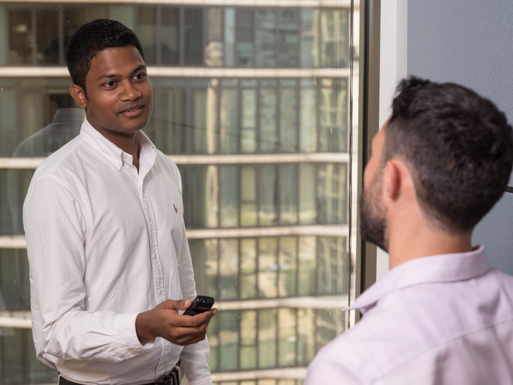 A student holds a recording device while he interviews someone. A high-rise building can be seen out the window.