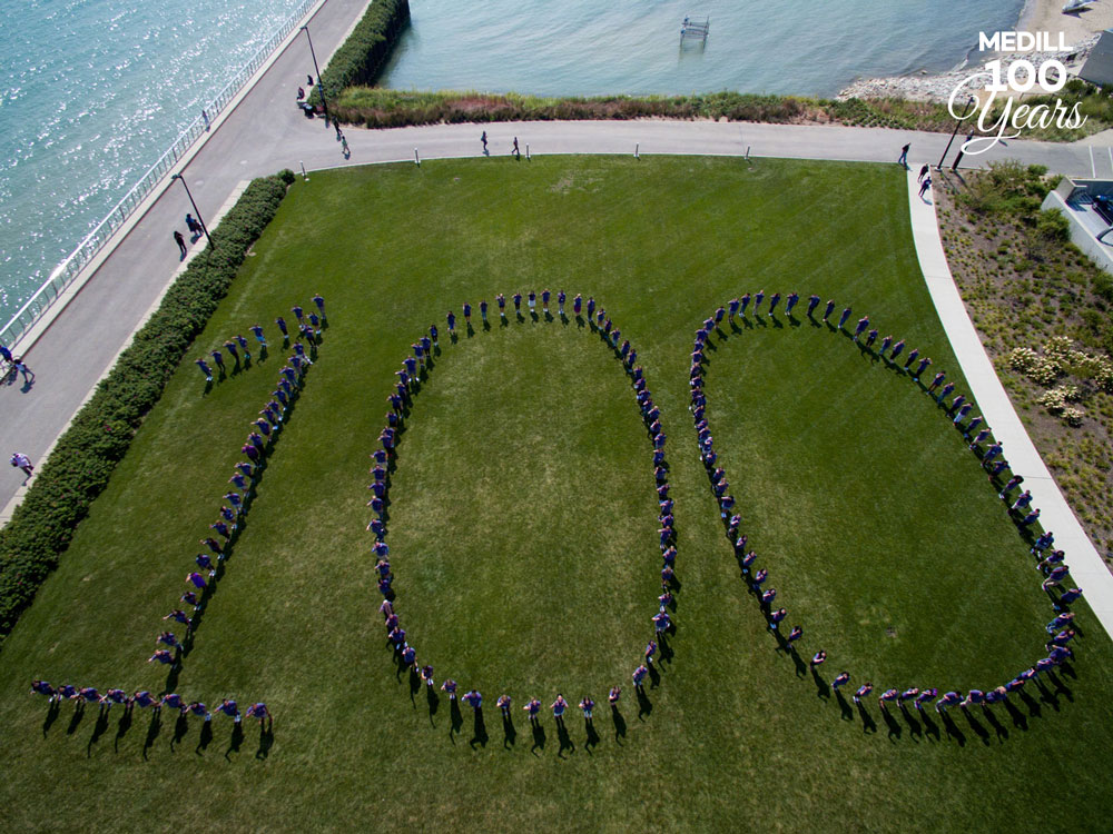"A large group of students wearing purple shirts form the number ""100."""