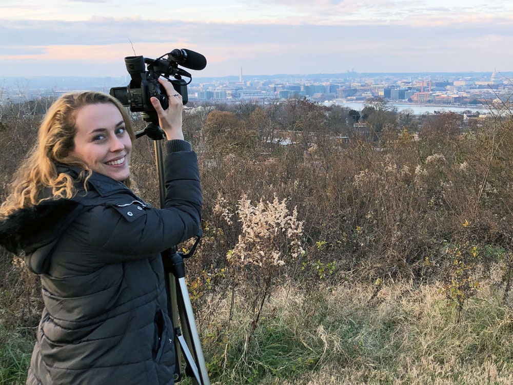A woman stands far back from a city and adjusts a camera to take a photo of the skyline
