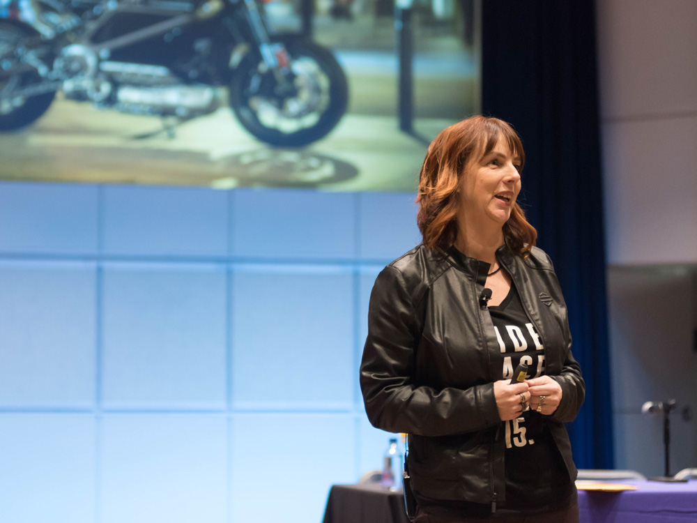 A woman stands on stage and speaks. A motorcycle is pictured on the screen behind her.