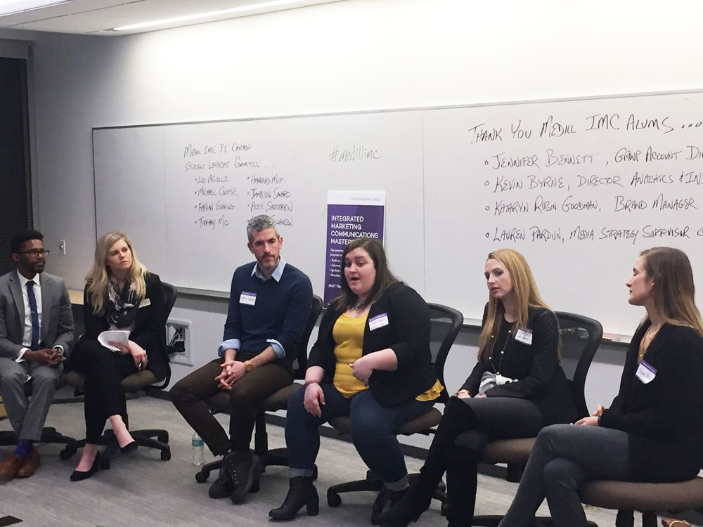Two Medill IMC students and four alumni sit at the front of a room and participate in a panel conversation