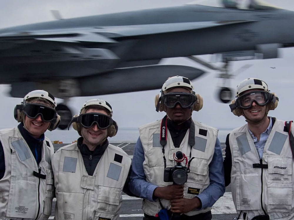 Four people stand wearing helmets, protective glasses and ear protectors onboard a U.S. Naval aircraft carrier