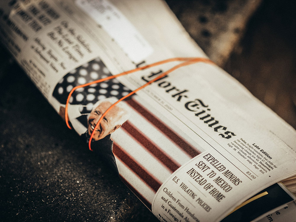 A rolled up issue of the New York Times displays an image of Joe Biden in front of an American flag backdrop.