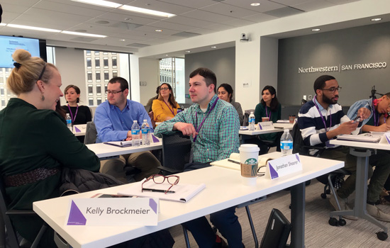 Students sit at tables and work together during the IMC MarTech course in San Francisco