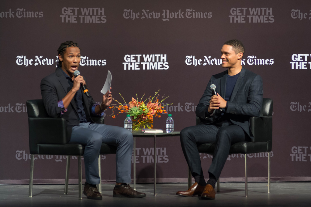 Medill alumnus John Eligon asks Trevor Noah a question on stage