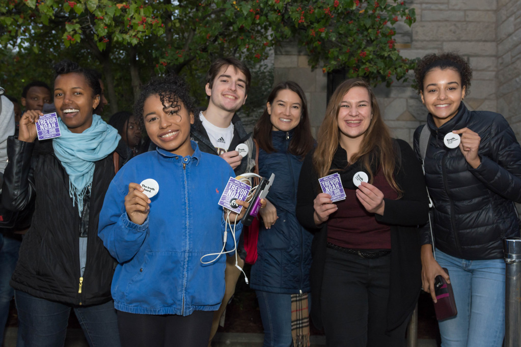 Students hold up giveaway items they received from Medill and The New York Times such as buttons and stickers