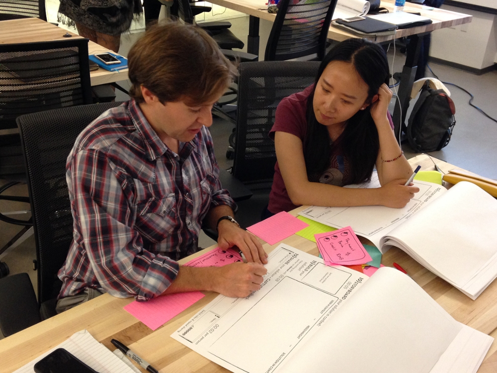 Two students work on a design exercise during class