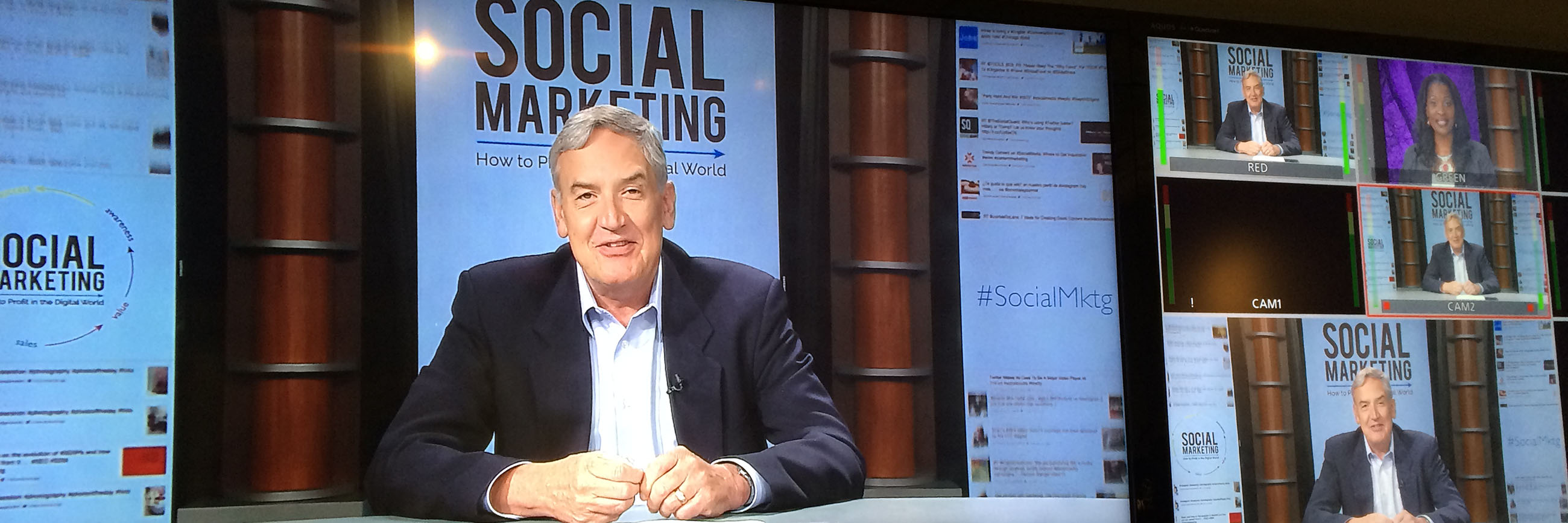 Presenter speaking at a desk with signs that say social marketing behind him